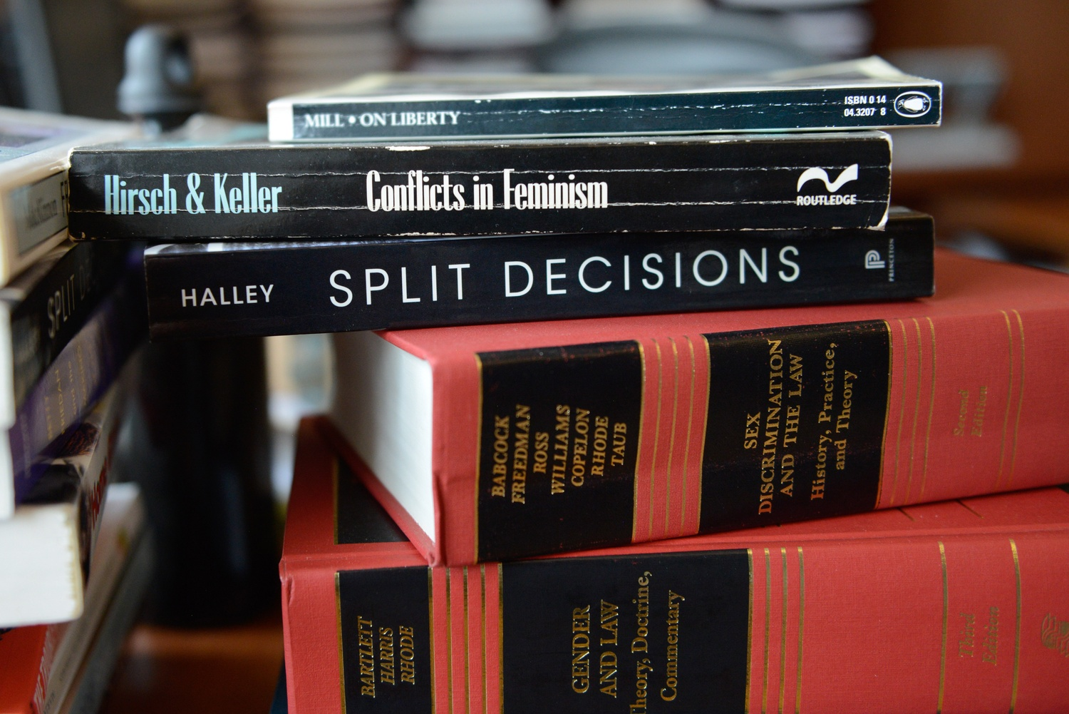 A collection of books—including her own—on topics including law, gender, and sexuality sit on Harvard Law School professor Janet Halley's desk.