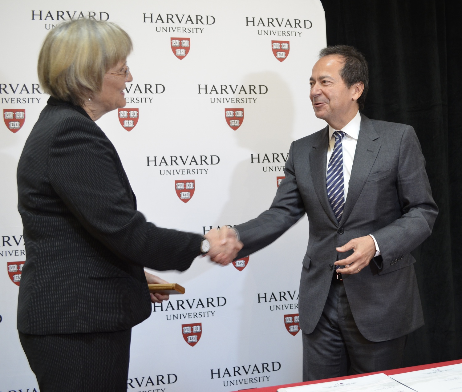 University President Drew G. Faust and hedge fund magnate John A. Paulson shake hands at an event announcing Paulson's $400 million gift to the School of Engineering and Applied Sciences.