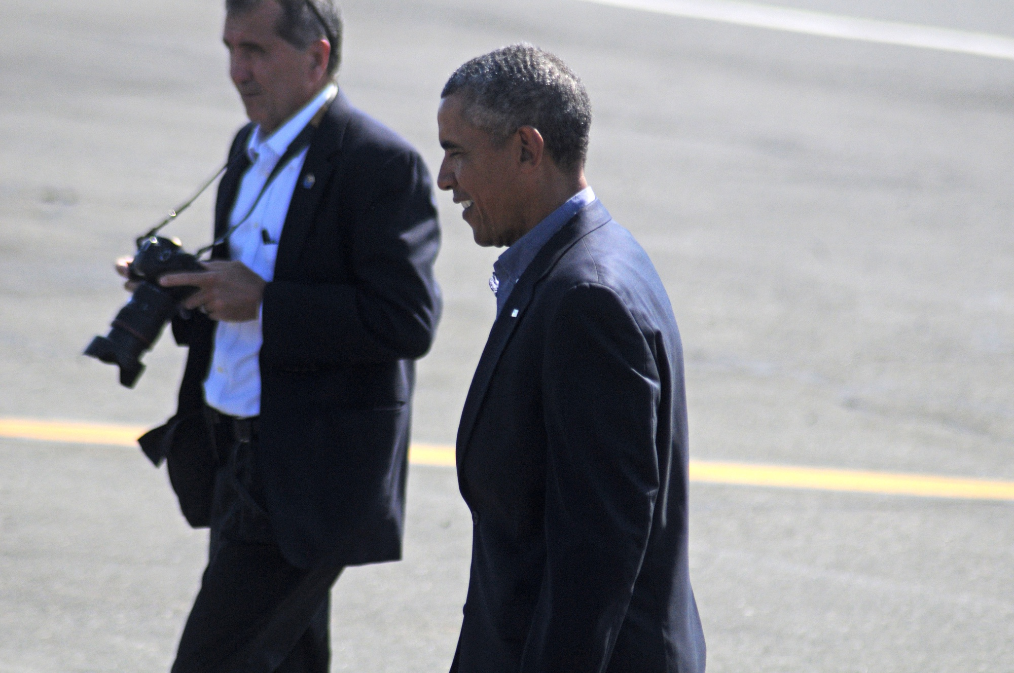President Barack Obama walks across the tarmac after arriving in Boston on Monday.