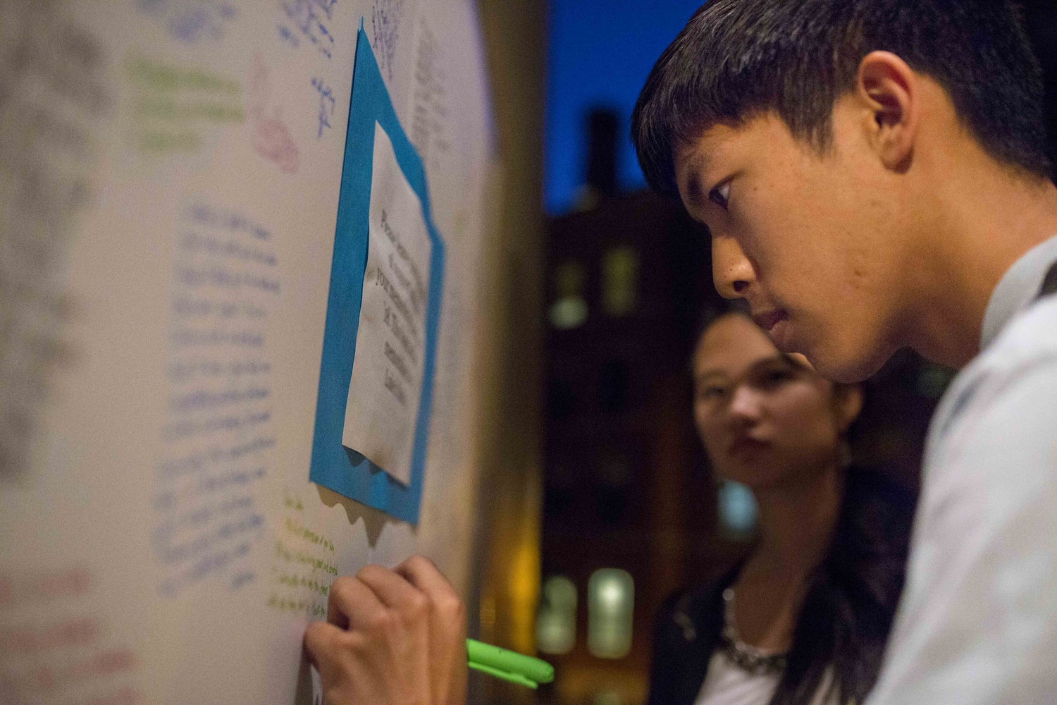 Molly J. Zhao '17, left, looks on as Reece V. Akana '17, right, writes a message on a board outside Memorial Church to Luke Z. Tang '18, who died last Saturday. On Wednesday, students, faculty, and family members gathered in Memorial Church to commemorate Tang.