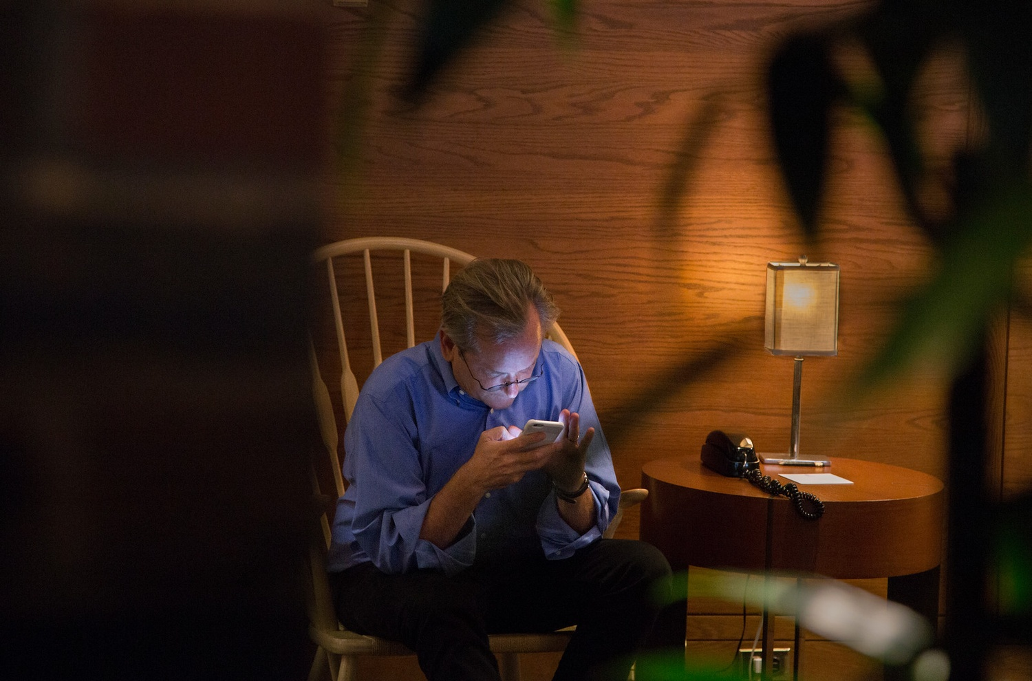 Harvard Law School professor Larry Lessig works on his cell phone in the lobby of the Charles Hotel. Lessig, who announced his presidential bid in early September, had been traveling extensively and was anxious about booking a last-minute flight to Washington, D.C.