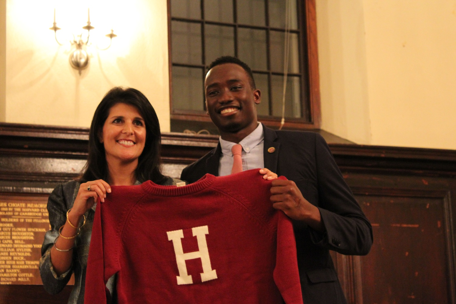 "South Carolina Governor Nikki R. Haley is presented with a Harvard ""letter sweater"" by Harvard Foundation intern Nuha Saho '18 at the conclusion of the dinner event where she was invited to make remarks Thursday night. Haley spoke with pride about the idea of a ""New South"" that promoted racial and economic equality and defended the Republican Party from accusations of racism and intolerance."
