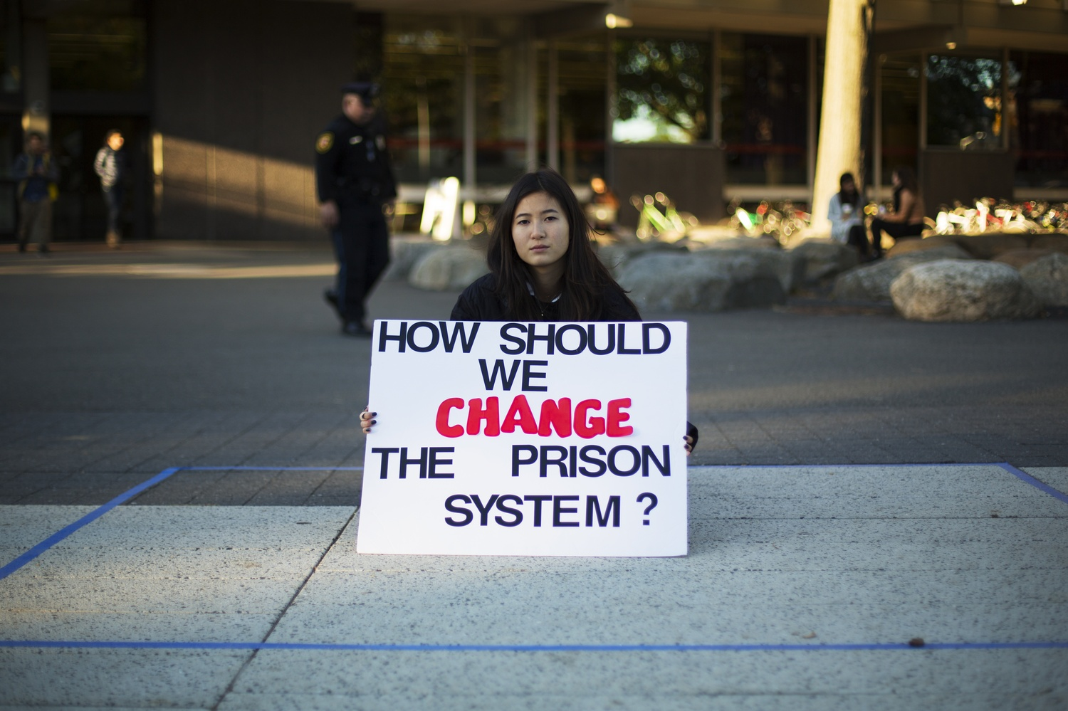 Michelle L. Kim '18 holds a silent vigil against solitary confinement on the Science Center Plaza Thursday. Harvard Undergraduate Organization for Prison Education and Reform installed a seven foot by nine foot rectangle on the plaza to raise awareness of solitary confinement.