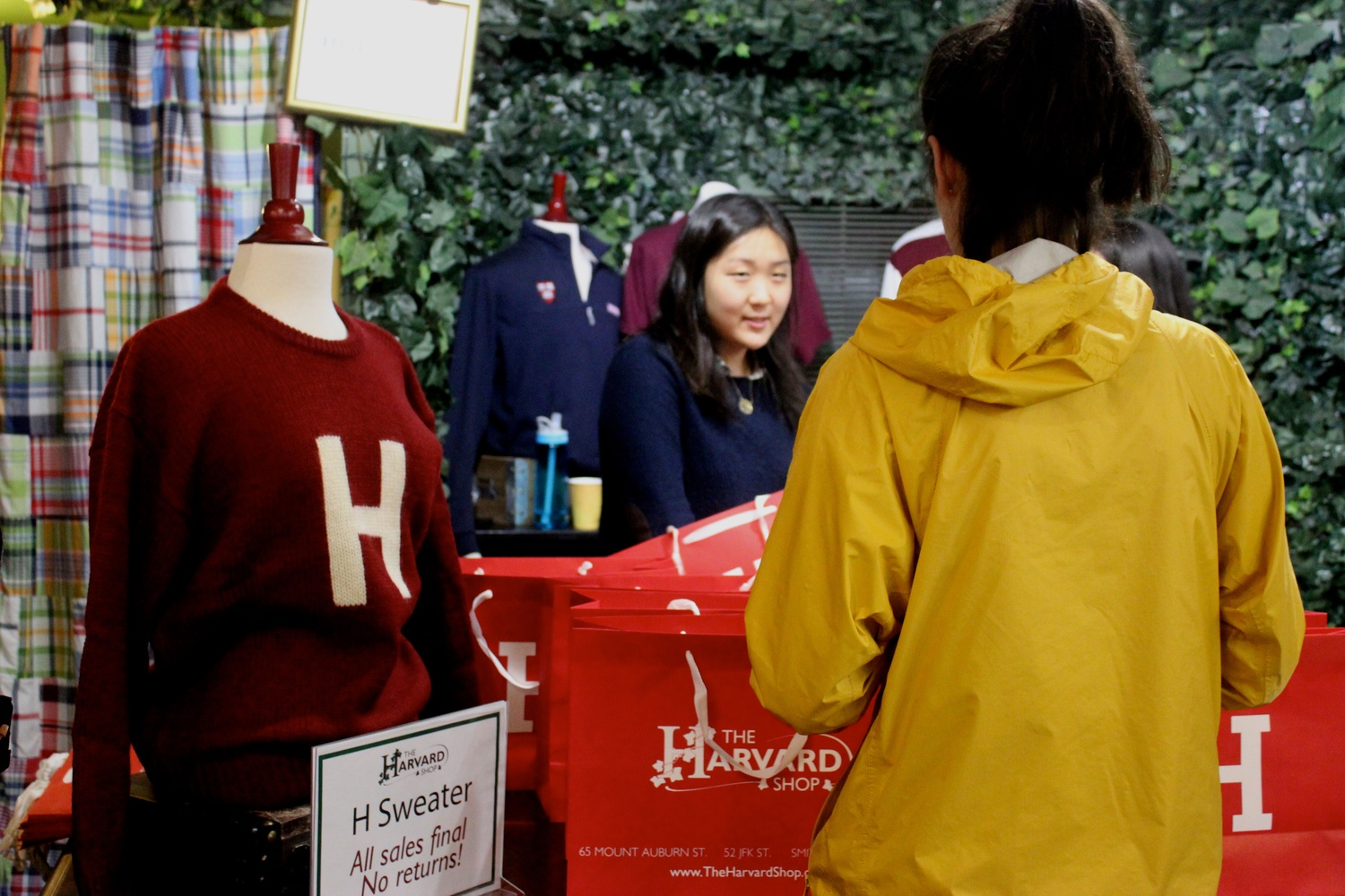 Diana Im '17, an employee at HSA's Harvard Shop, prepares to give a student her H sweater at the sweater's release party in late September.