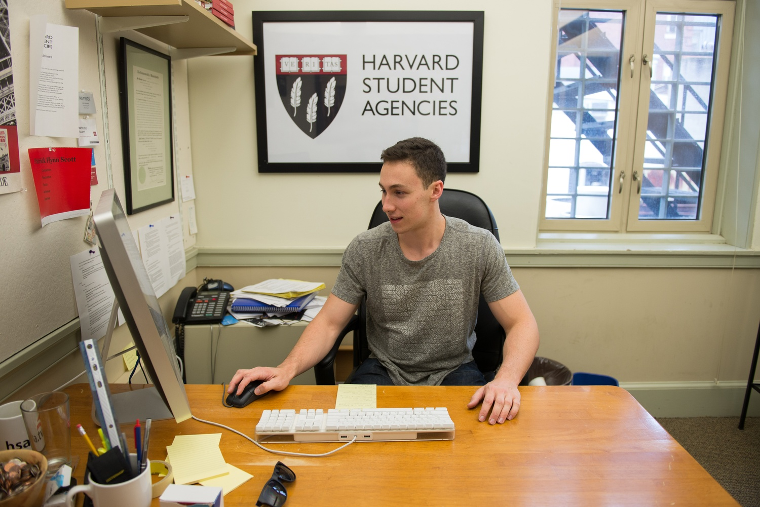 Patrick F. Scott '16, president of Harvard Student Agencies, responds to e-mails in his office in the HSA building. Scott first joined the organization as a laundry deliverer.
