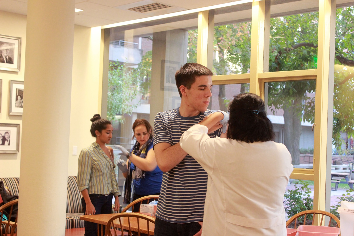 Steve A. Buschbach '16 braces for a flu shot in Quincy. Harvard HealthPals sponsored the event, which will occur at various locations around campus in the coming weeks.