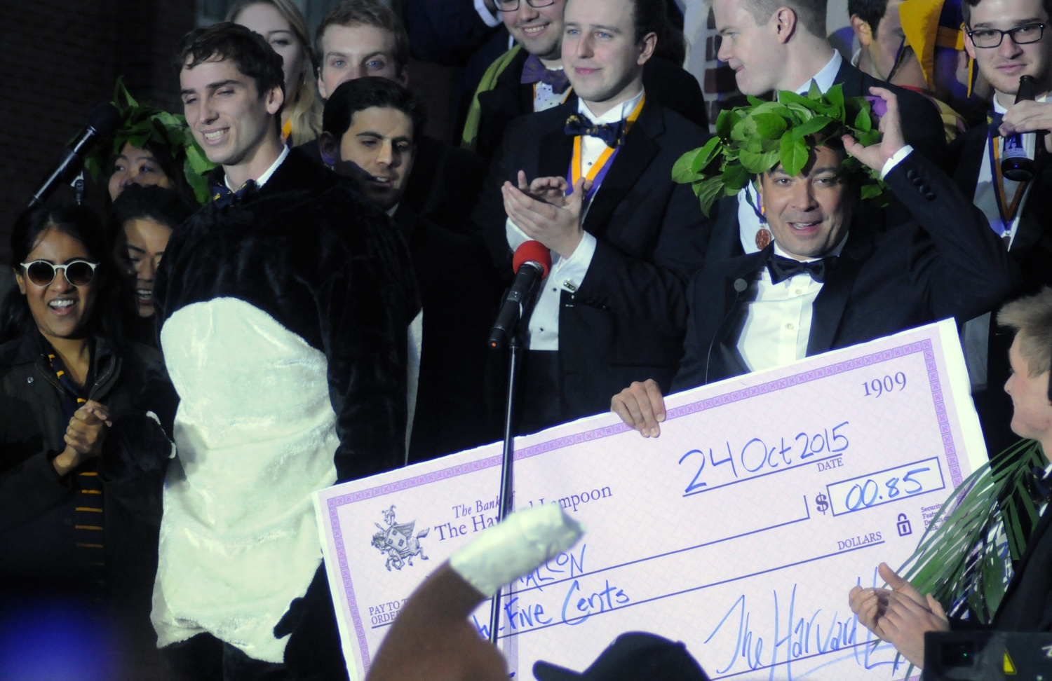 """Jimmy Fallon, host of """"The Tonight Show,"""" accepts a check for $0.85 from the Harvard Lampoon on Saturday afternoon."""