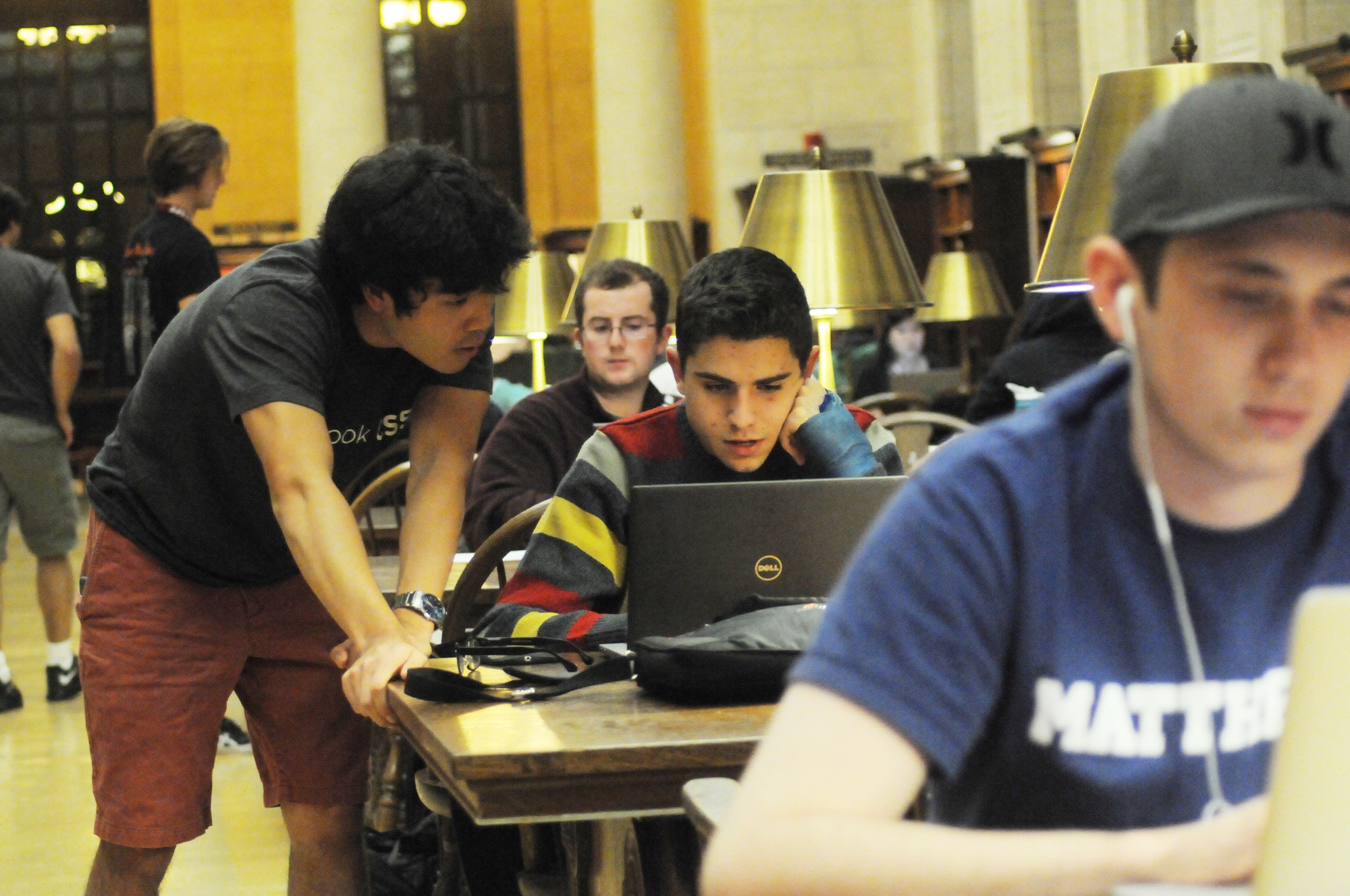 Jordan H. Hayashi, left, a teaching fellow for CS50, assists a student during CS50 office hours in Widener Library on Monday evening.