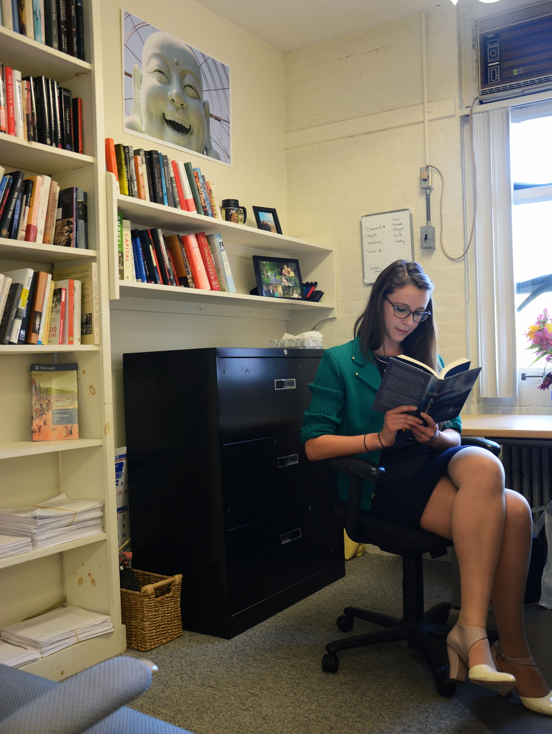 "Amanda Peery '14, an English concentrator, opens a book to read in her office at Harvard University Press. Peery said than a career in publishing ""doesn't start in college at all in the sense that you will have a job lined up when you graduate from college... There's no straight path like there is for finance or consulting."""