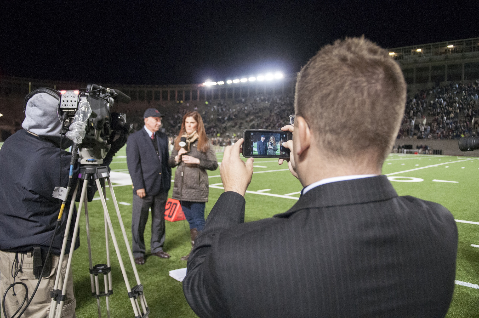 Tim Williamson, right, films on his phone while a Fox College Sports reporter interviews Director of Athletics Bob Scalise during halftime of the Harvard-Brown football game in late September.