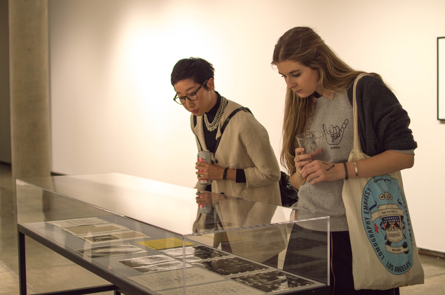 """""""It feels like you're going to two shows,"""" said Harvard Art Museums Curatorial Assistant Jessica S. Hong about the simultaneous opening of two new exhibits on Thursday evening. Hong, left, and Madi L. Stine '17 examine art during a new show in the third floor of the Carpenter Center."""