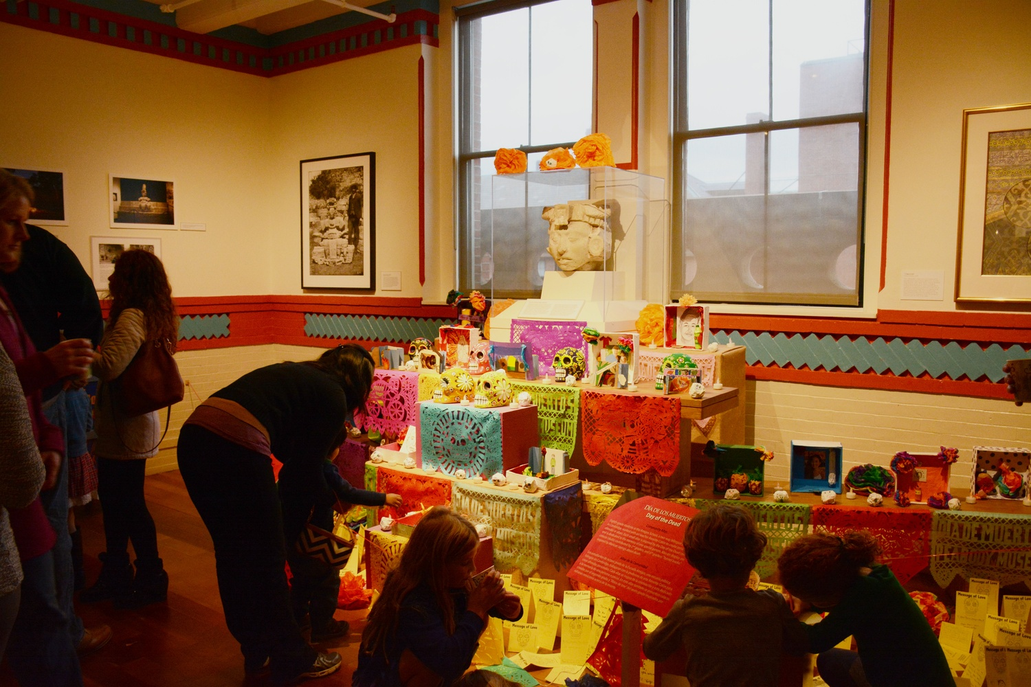 Peabody Museum visitors examine a table full of objects associated with the Day of the Dead.  This setup is part of the Peabody Museum's celebration of the Day of the Dead for local families.