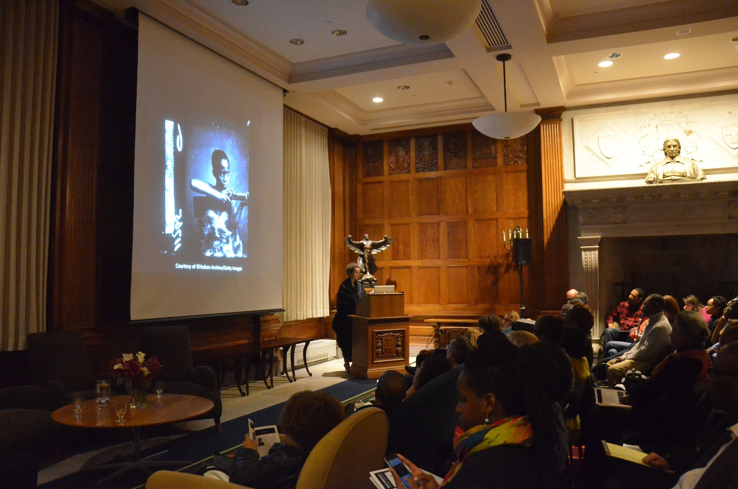 """Renée Mussai, a curator and scholar on the African diaspora and Black British photographic history, speaks about photograph """"Zulu Boy"""" as part of the Black Chronicles II Symposium in the Hutchins Center on Monday evening."""