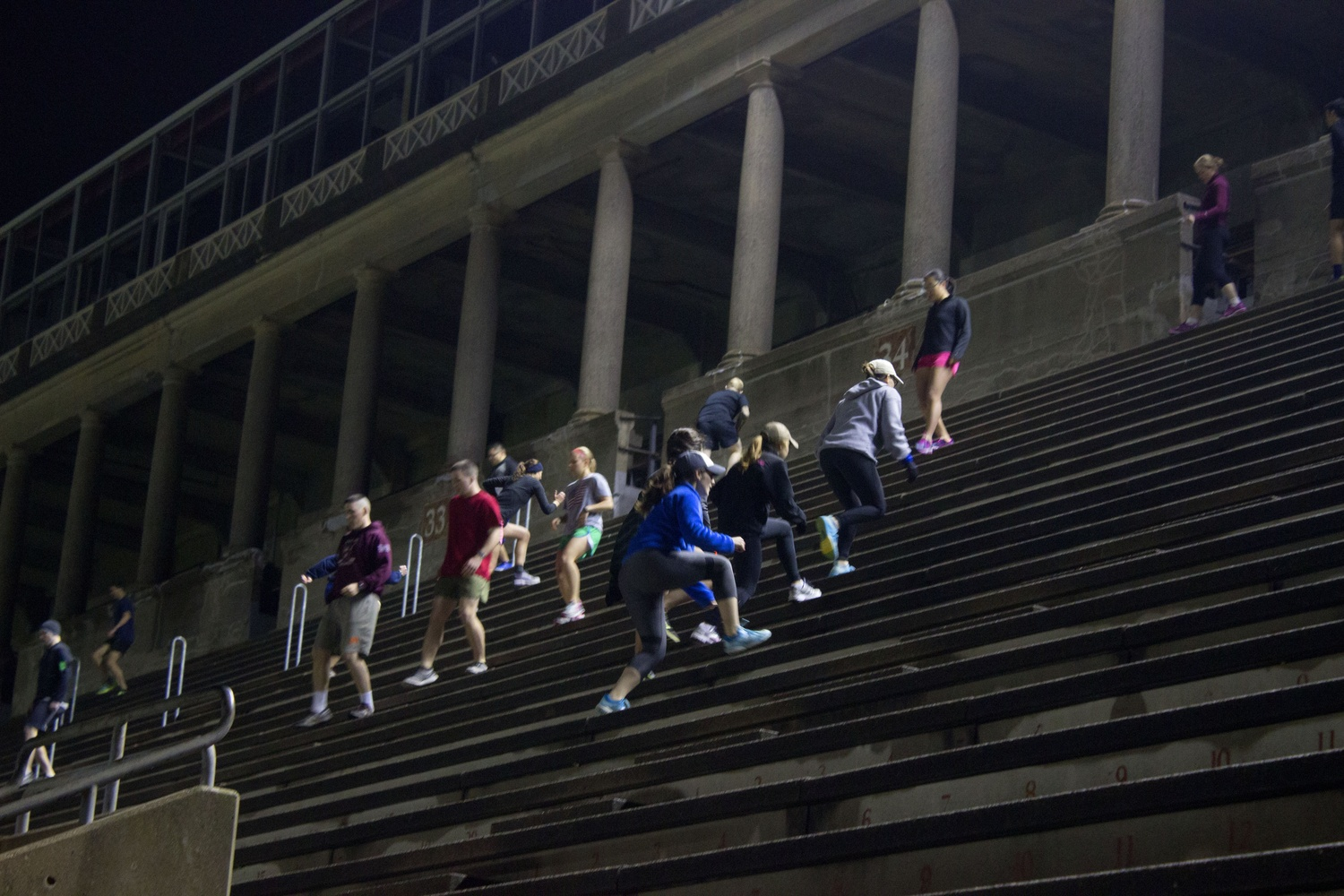 Veterans, students in ROTC, and supportive community members begin running up the steps of Harvard Stadium. They gathered on Veteran's Day to support past and present veterans and raise money for the Warrior Scholar Project.