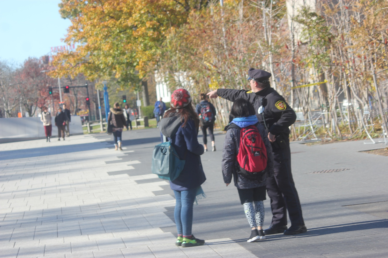 A member of the Harvard University Police Department directs people away from Harvard Yard and the Science Center after students were sent an alert of an unconfirmed bomb threat.
