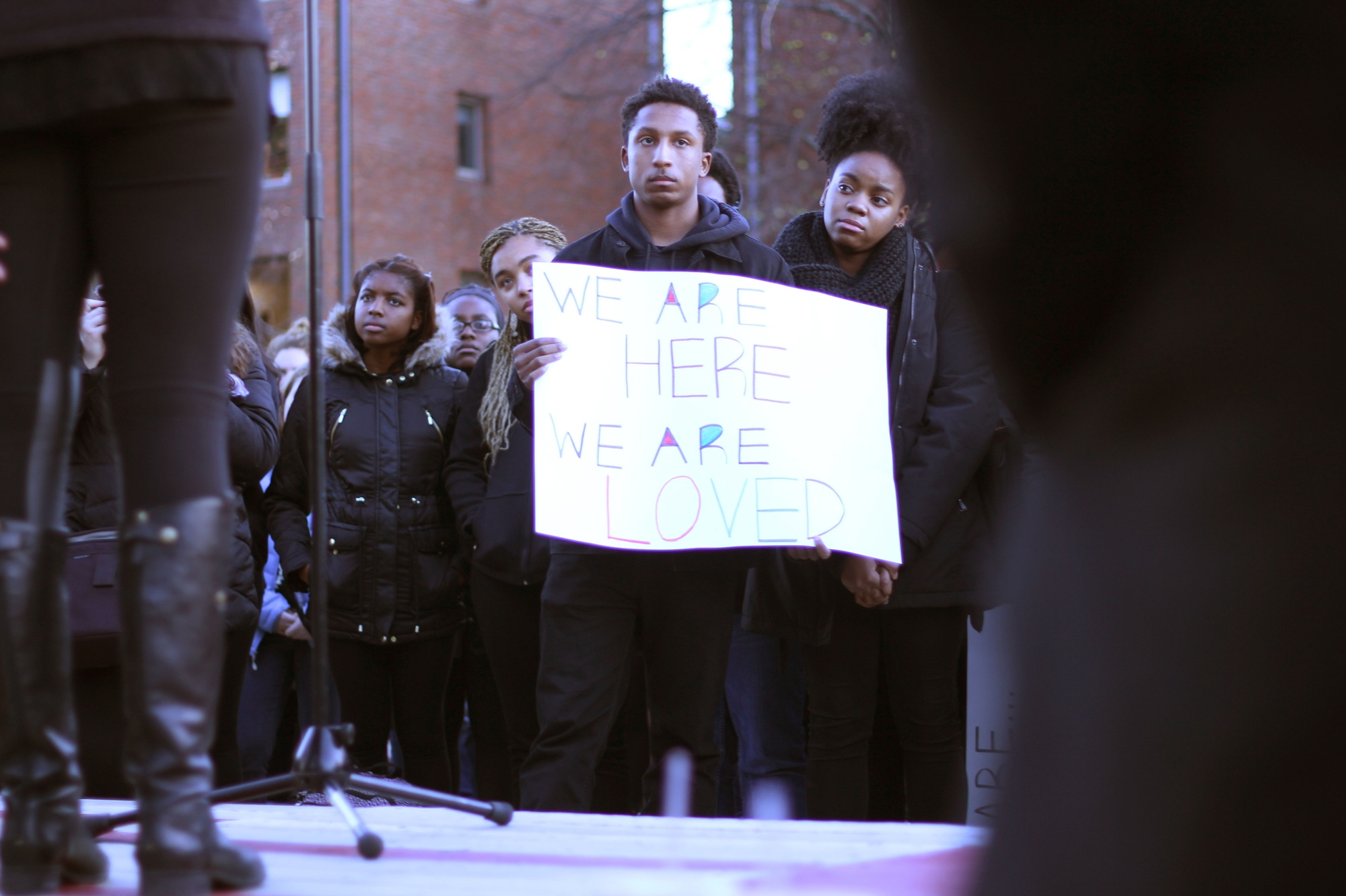 Hasani A. Hayden '19 holds up a banner during a rally at the Science Center in November.  Students rallied and marched to Porter Square in support of black student activists at peer schools such as Yale and the University of Missouri.