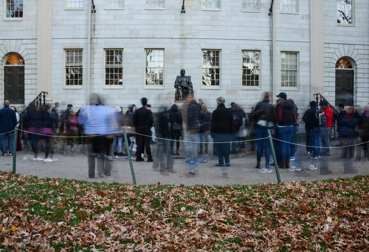 A stream of tourists passes John Harvard Statue, a famous tourist destination of the campus and Boston itself. The statue is the third most photographed in the US behind the Statue of Liberty and the Lincoln Memorial.