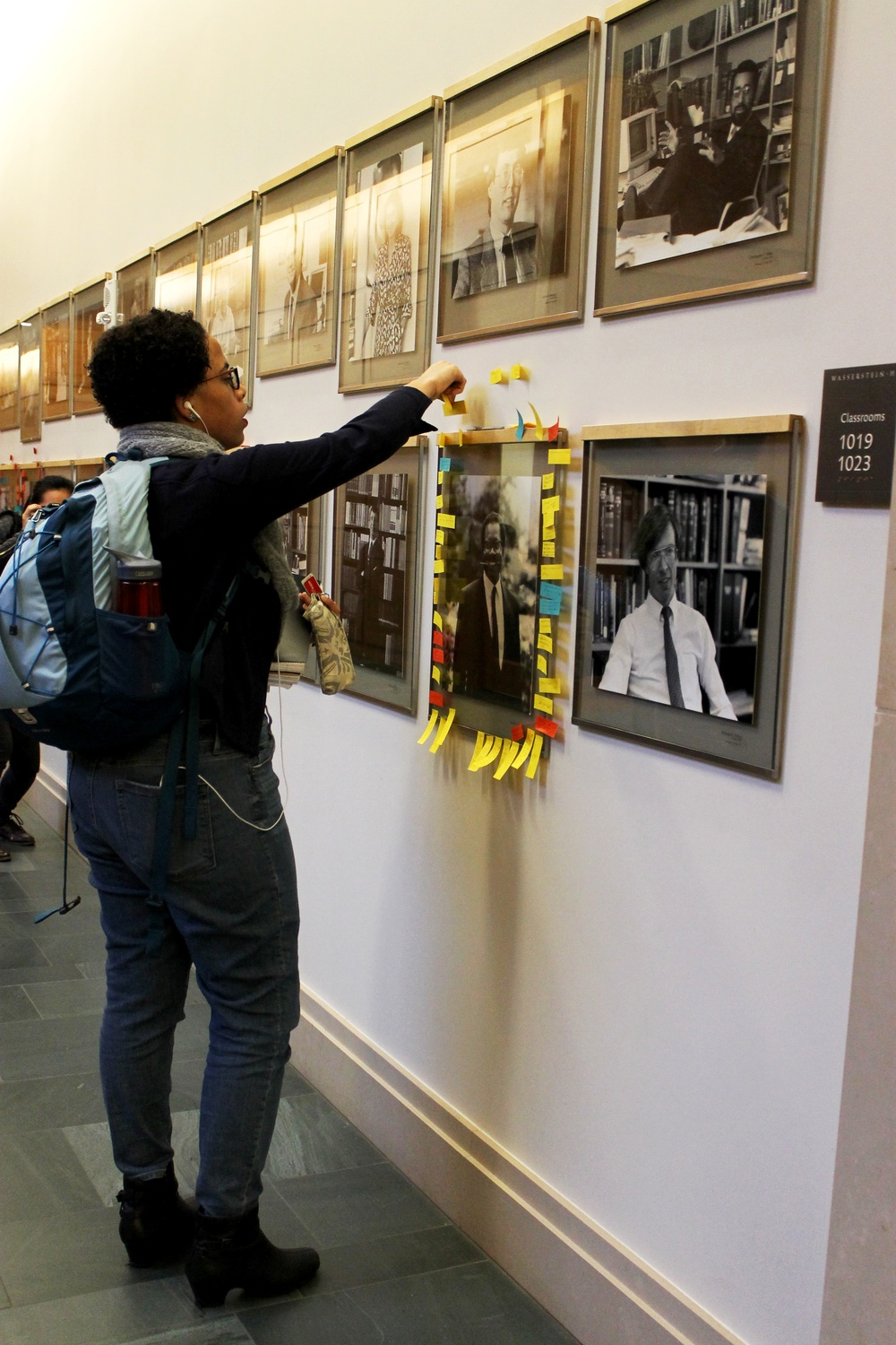 Tori Anderson, a third-year Harvard Law School student, adds a sticky note to the portrait of a black Law School professor on Thursday in a motion of support for the faculty.