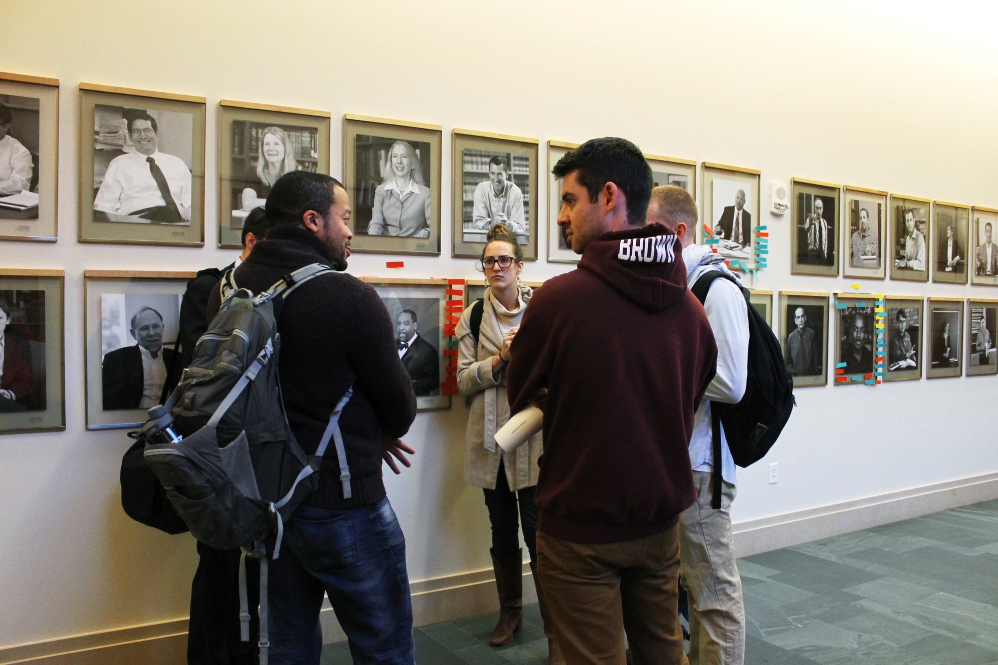 A group of Law School students discusses the vandalism on the portraits of black Law School professors in front of the portraits on the first floor of Wasserstein Hall in the afternoon.