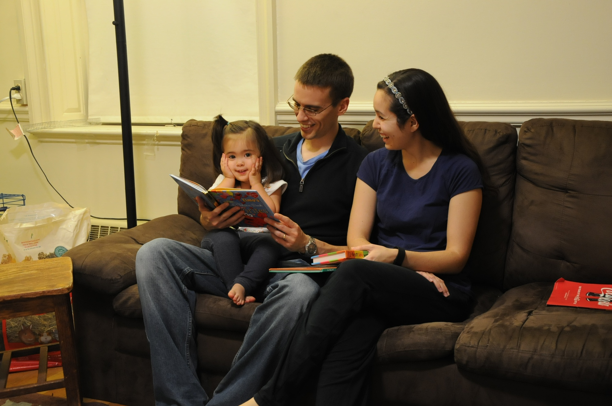 The daughter of proctors Alex and Celeste Douglas reads an Elmo book with her parents in Lionel A.