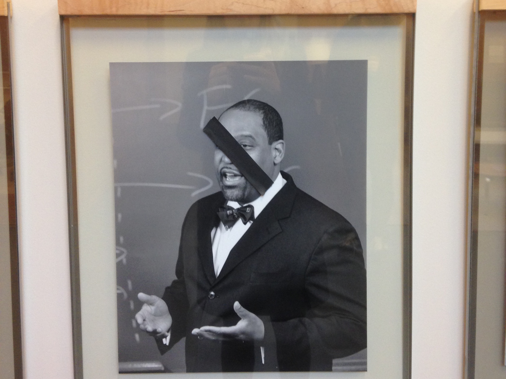 Photos of black Law School professors were covered by pieces of black tape on Thursday morning at Wasserstein Hall.