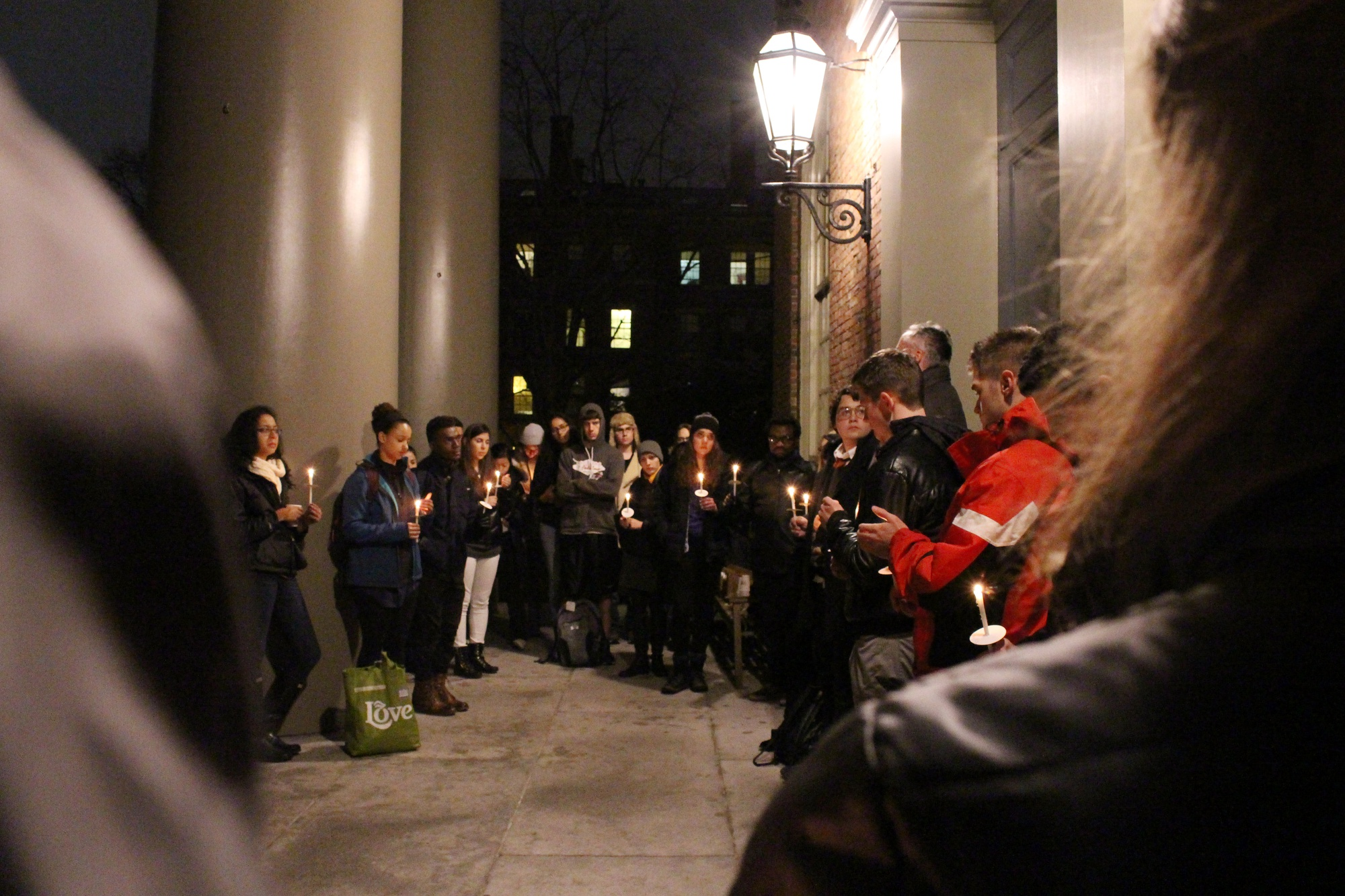 Students stand during a moment of silence at the end of the AIDS Day vigil on Tuesday night.