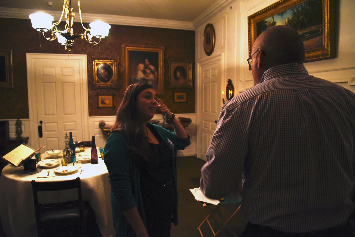 Marissa Cheifetz, a member of the Longfellow holiday open house's staff, describes the Longfellows' holiday menu to a visitor at Friday evening's open house.