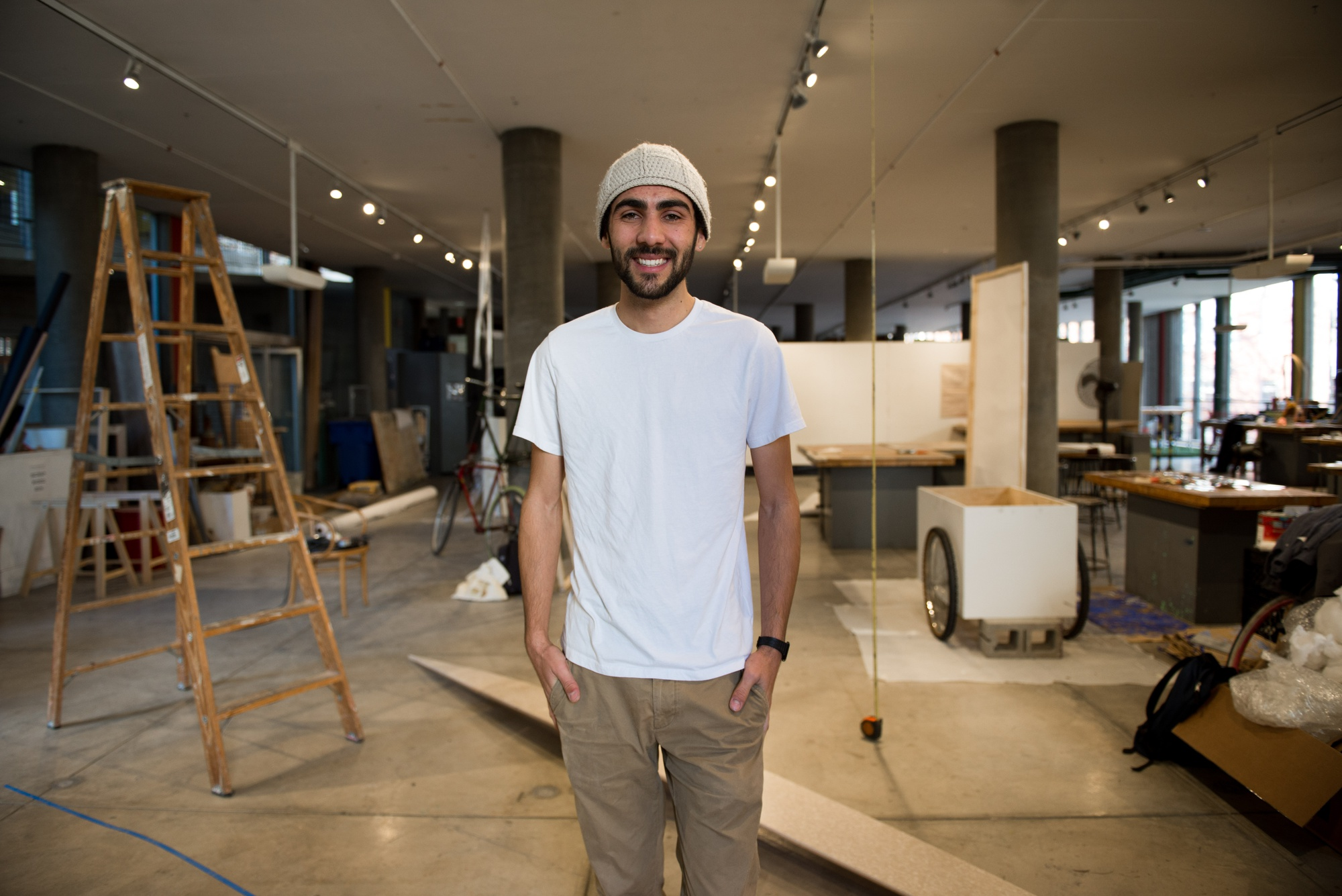 """Orman poses in front of his work area in the Carpenter Center, which is covered in his works-in-progress and completed sculptures. """"I used to take up the entire area,"""" said Orman, claiming he is """"basically an artist in residence."""""""