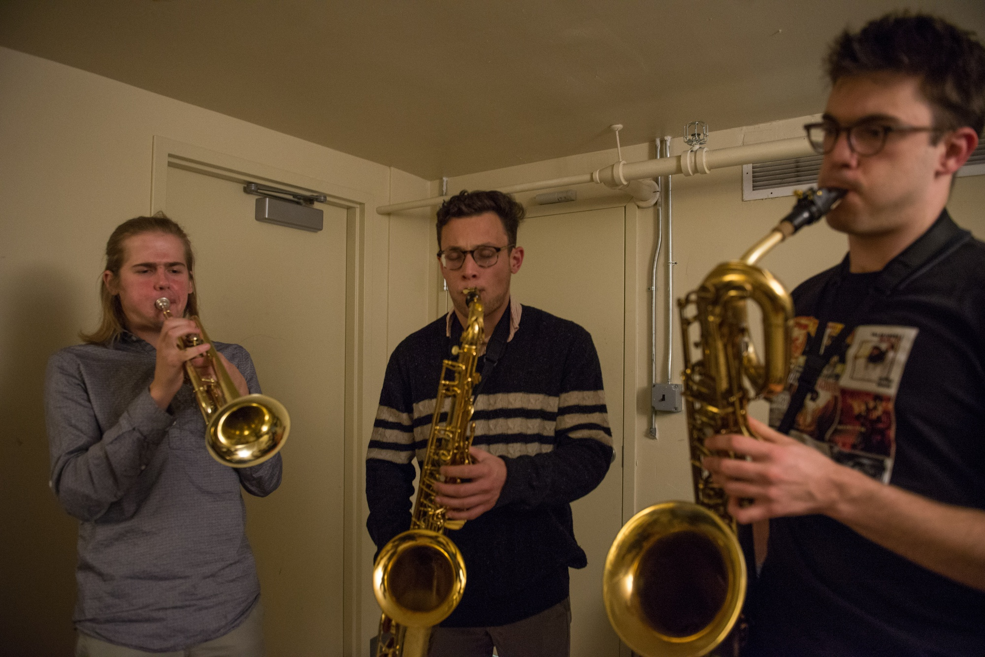 Tree A. Palmedo '16, Ben L. Sobel '16, and John B. Tournas '16 play trumpet and sax during an Intrinsics rehearsal in Lowell basement.