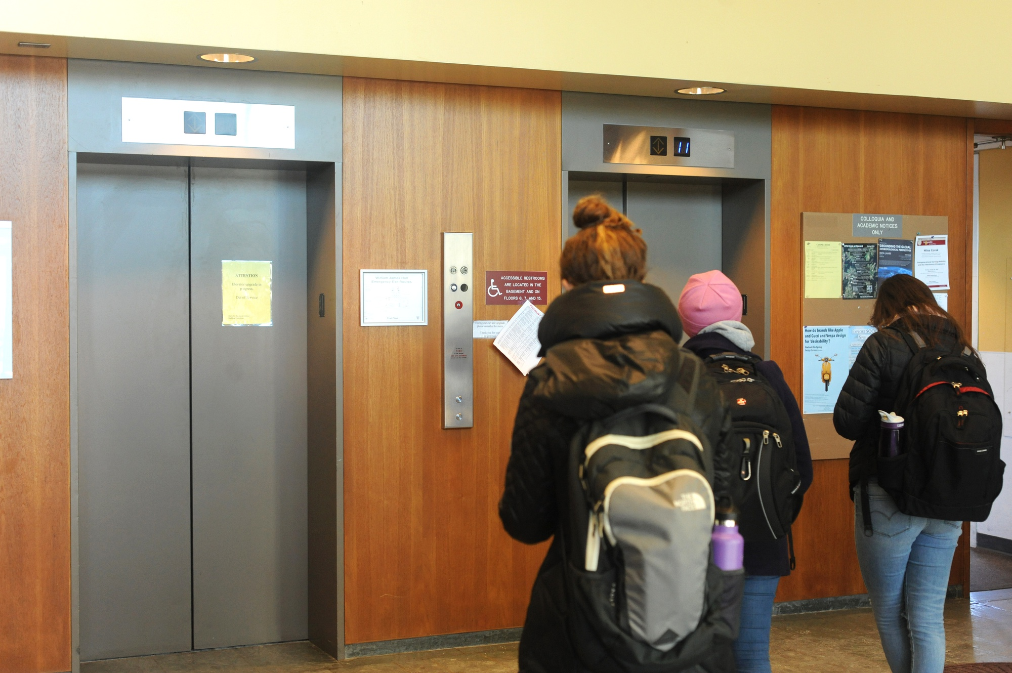 Students wait for one of the two working elevators in Harvard's William James Hall to arrive on the first floor Monday afternoon. The building's three elevators are undergoing repairs one at a time.