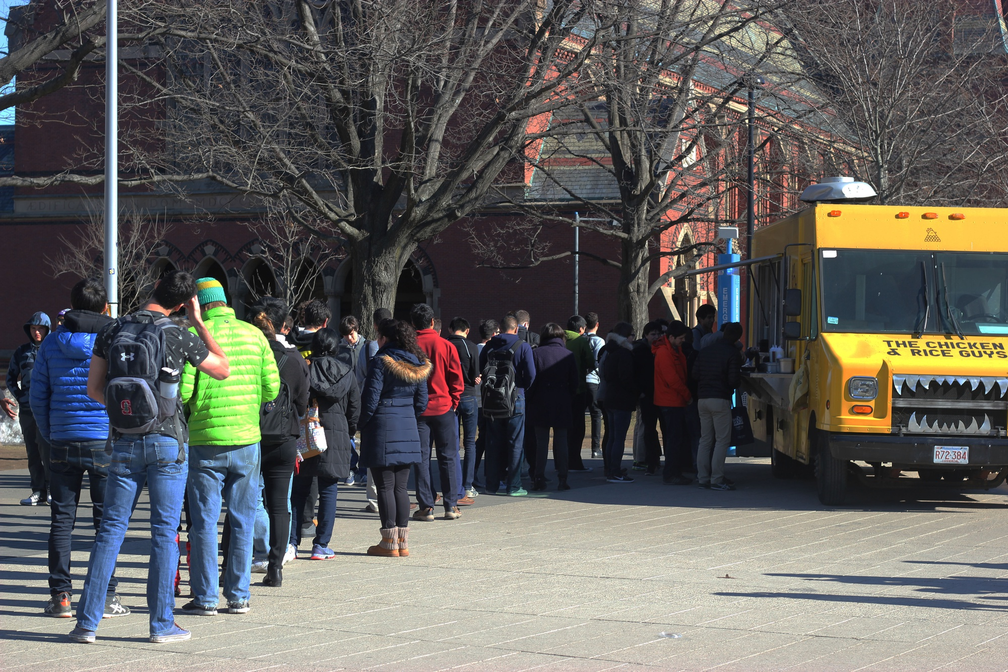 A line forms outside of the Chicken and Rice Guys food truck at the Science Center plaza. Northeastern students recently triumphed over Harvard in a Facebook competition that offered free snack size meals for a day to the winning study body.