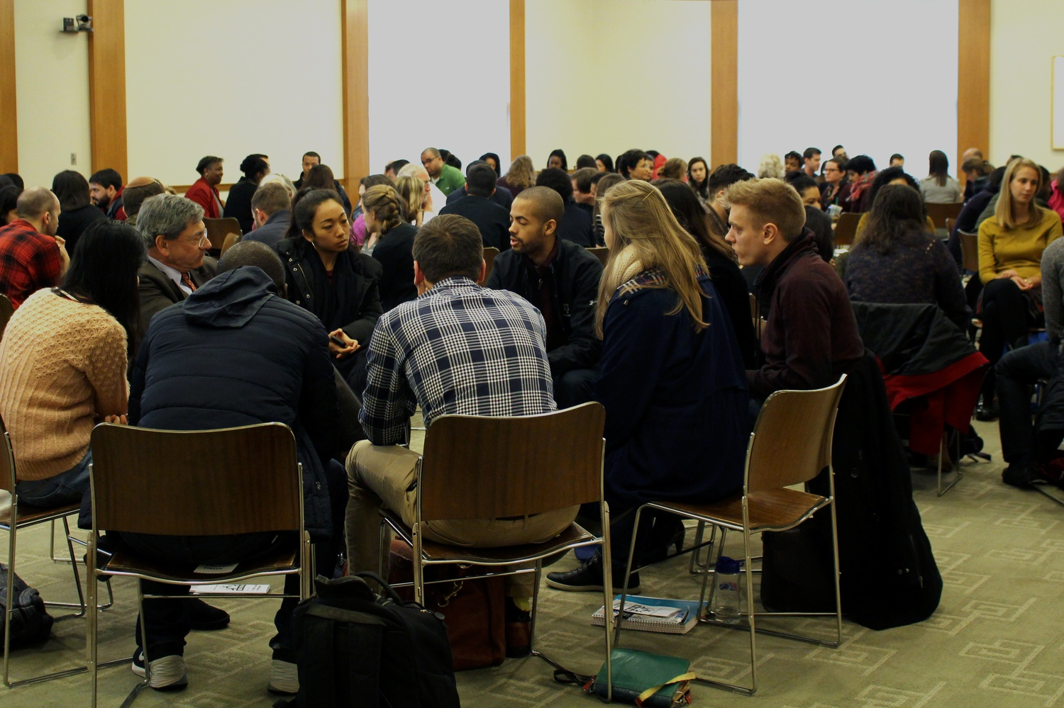 "Harvard Law School students participate in a meeting about the change of the Law School's shield on Thursday afternoon. A student organization called ""Royall Must Fall"" created last year protests the seal's alleged association to slavery."