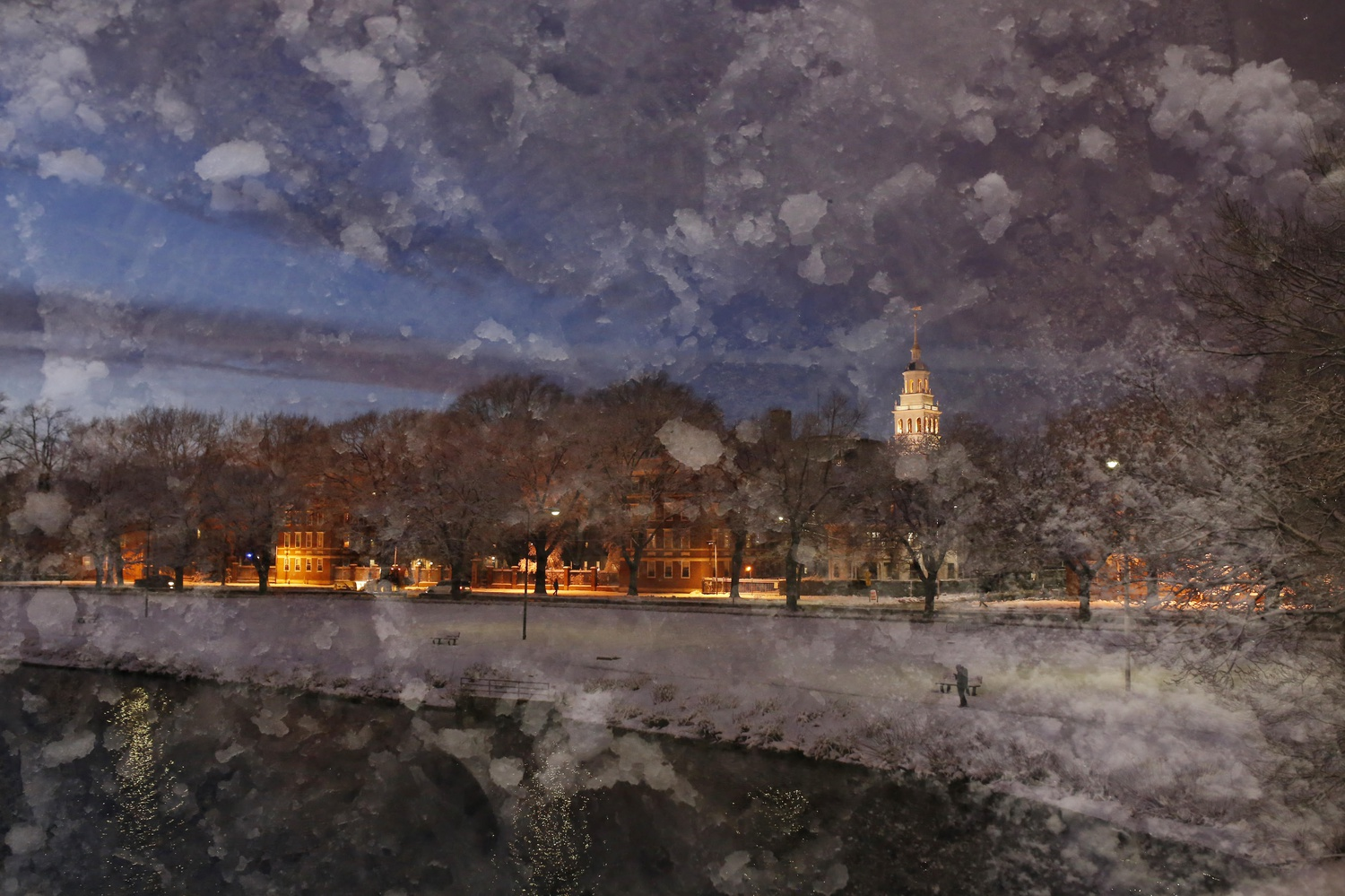 """An image of snow on Weeks Bridge overlays an image taken seconds prior showing the view of Lowell tower from the bridge on Friday evening. The photographer used her camera to combine the images, creating a """"double exposure."""""""