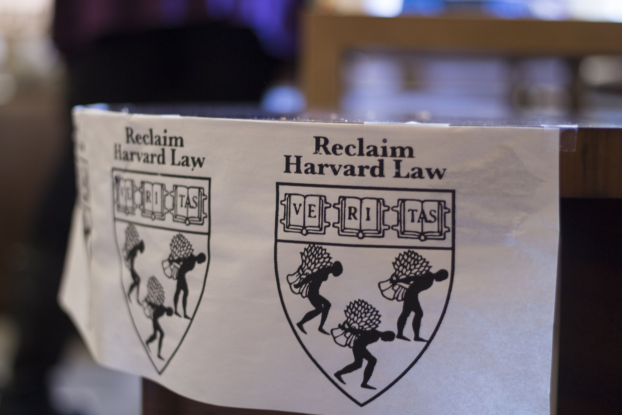 Harvard Law School students put up posters in the WCC on Tuesday afternoon as part of Reclaim Harvard Law's occupation.
