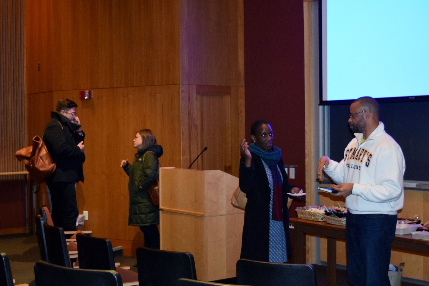"""People mingle after a talk on """"Transgender Genealogies"""" by University of Michigan professor Lawrence M. LaFountain-Stokes '90, pictured left."""