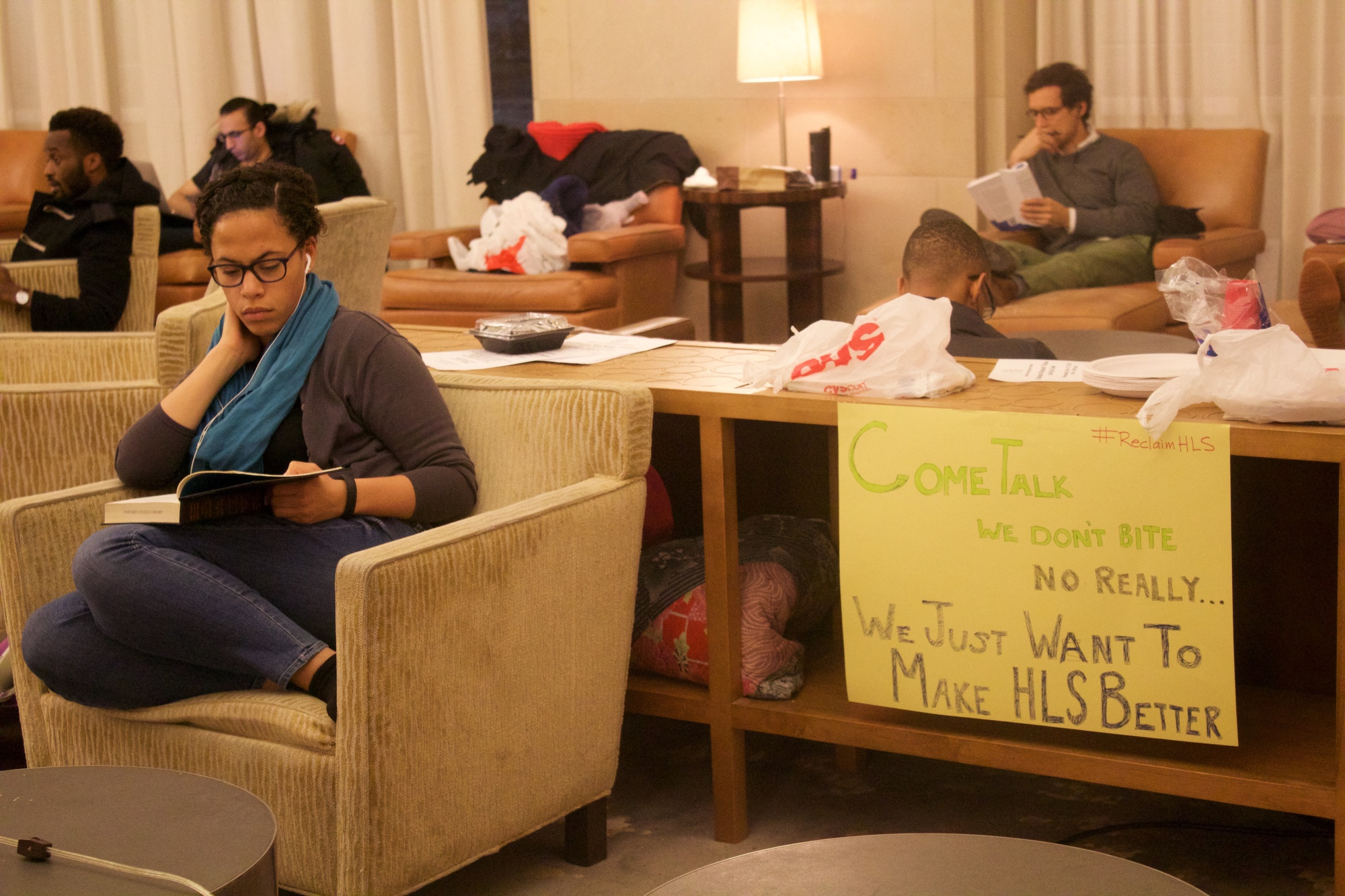 "Tori Anderson, a 3L at Harvard Law School, studies by a sign in the Caspersen Student Center lounge space that student activists renamed ""Belinda Hall"". Students held public teach-ins and spoke to passersby about their cause over the course of their occupation."