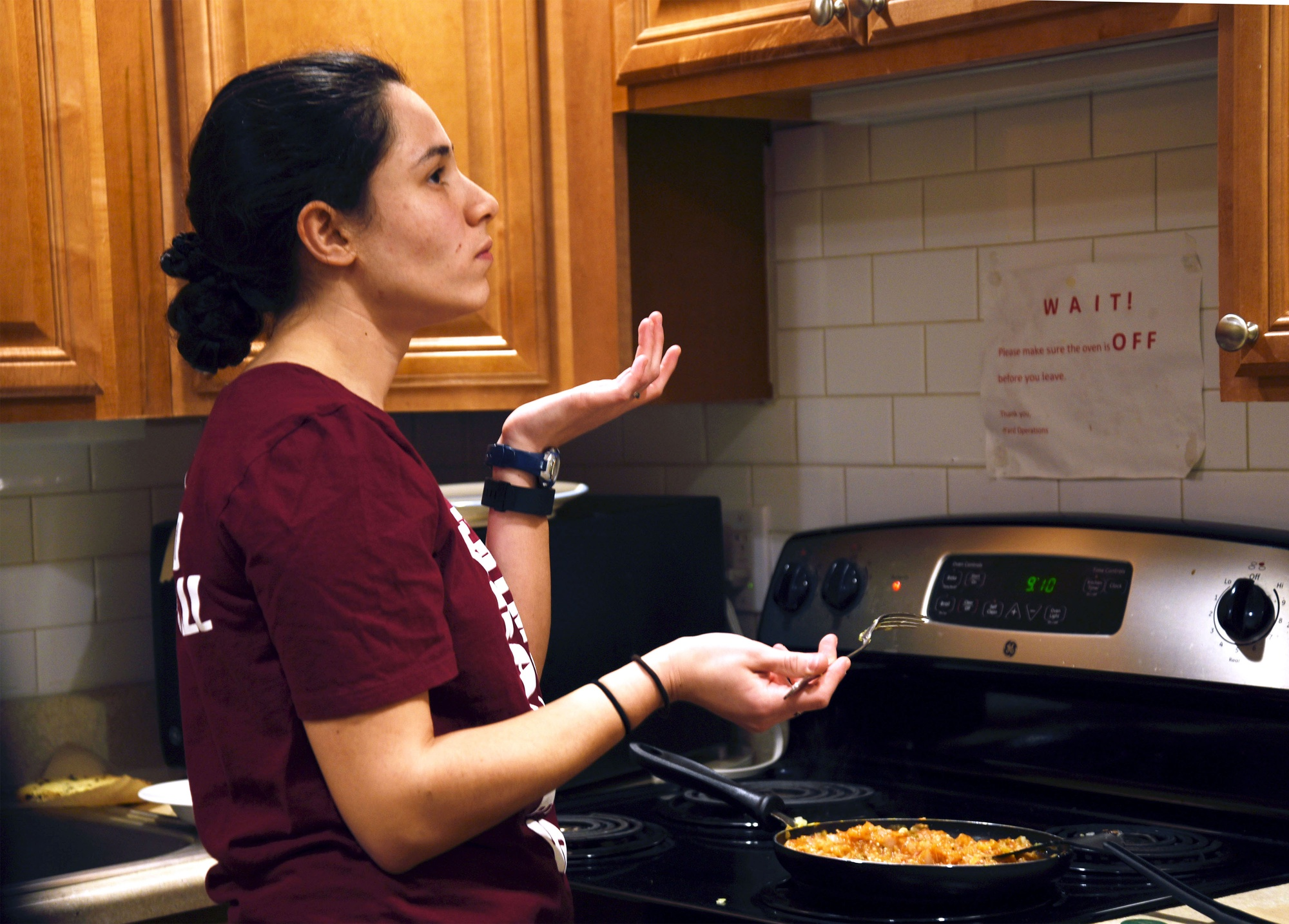 Athena Braun '19 tries a bite of her cooking while preparing a dish for food critic Bovey Rao '19 on Thursday evening.