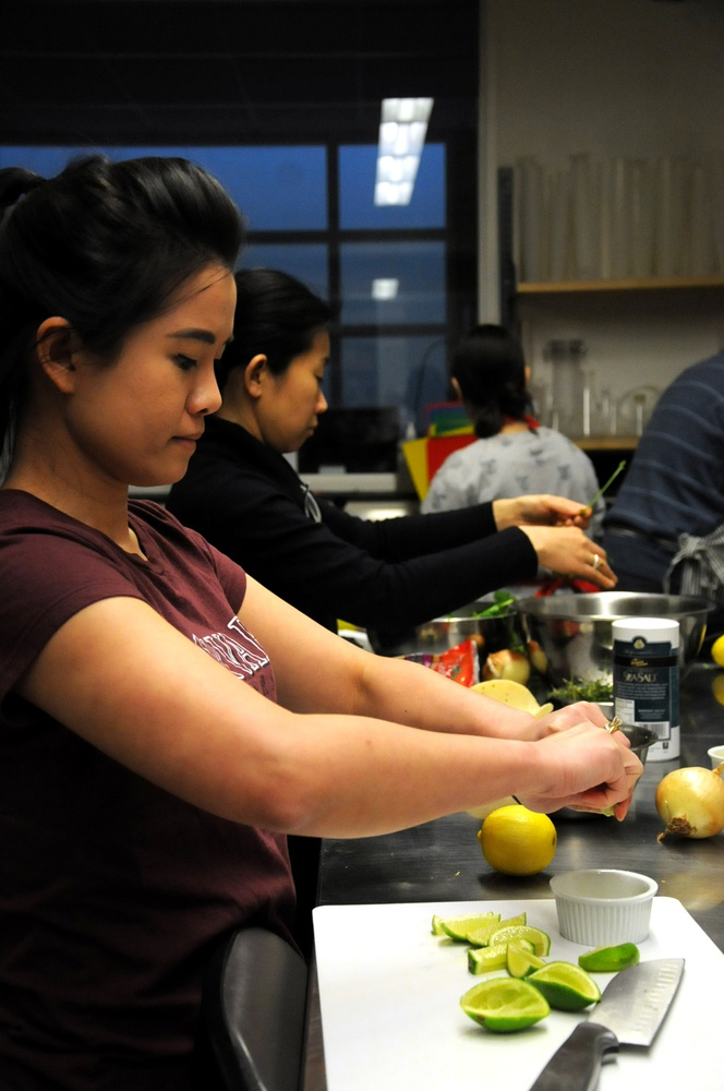 Harvard extension school graduate student Ploy Khunisorn takes part in this immersive learning experience by grating some limes and preparing for the final delicacy.