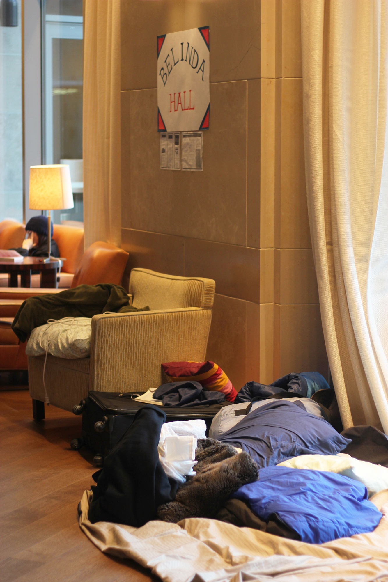 """Pillows, blankets, and suitcases cover the floor in the Law School's Caspersen Student Center lounge so student activists can continue to occupy the space as part of the Reclaim Harvard Law protests. The activists have now occupied the lounge, which they have dubbed """"Belinda Hall,"""" for three weeks and plan to continue the occupation for the foreseeable future."""