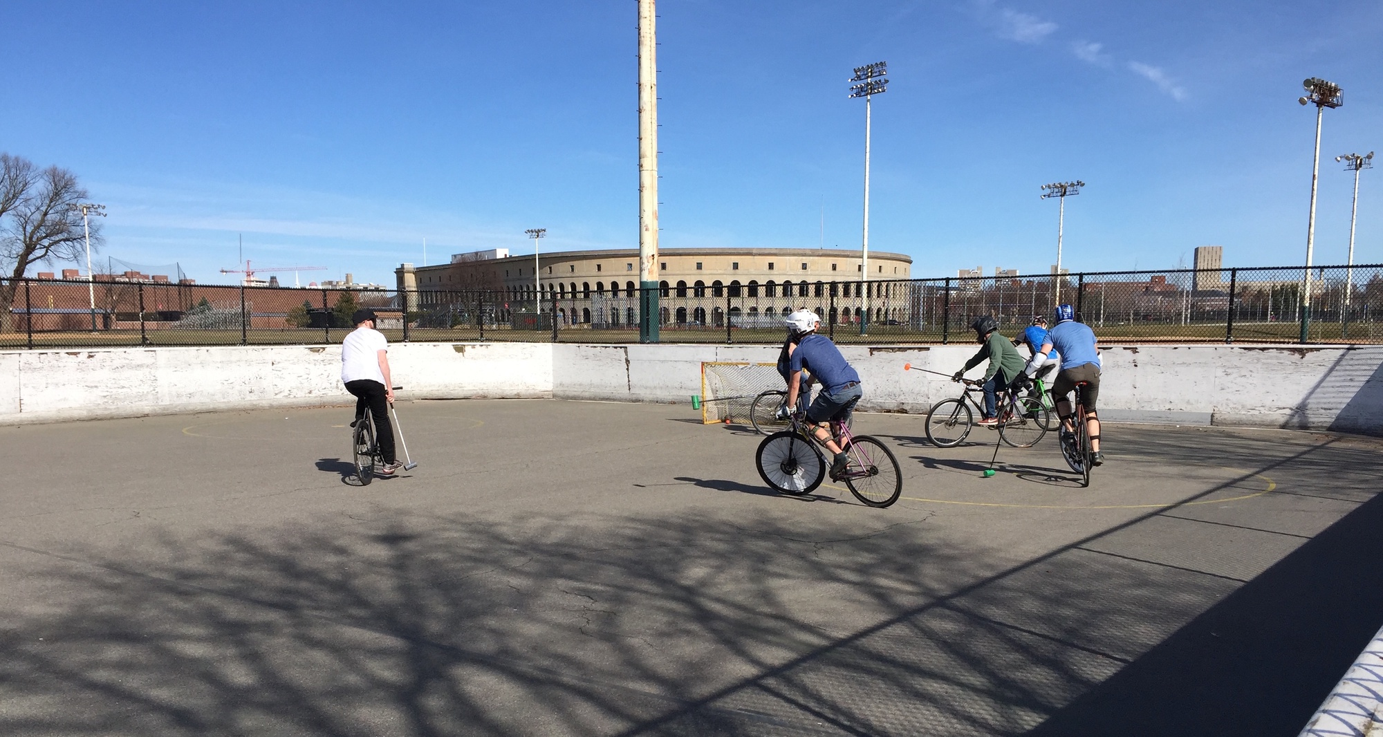 Members of the Boston Bike Polo club play an afternoon game of bike polo on the Smith Field park hockey court in Allston.