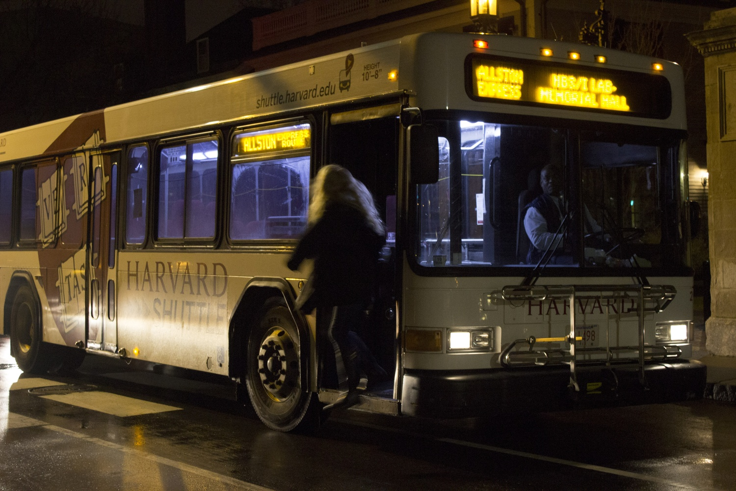 A Harvard University Allston shuttle makes a routine stop outside of Lamont Library Thursday evening.