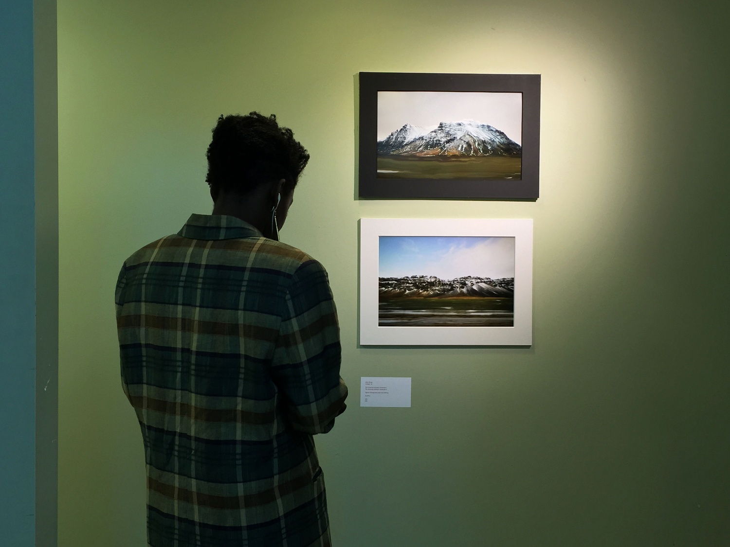 Abena Duker 18'-19' examines photographs at the Harvard Student Art Show, which ran from Friday through Sunday at 29 Garden Street.
