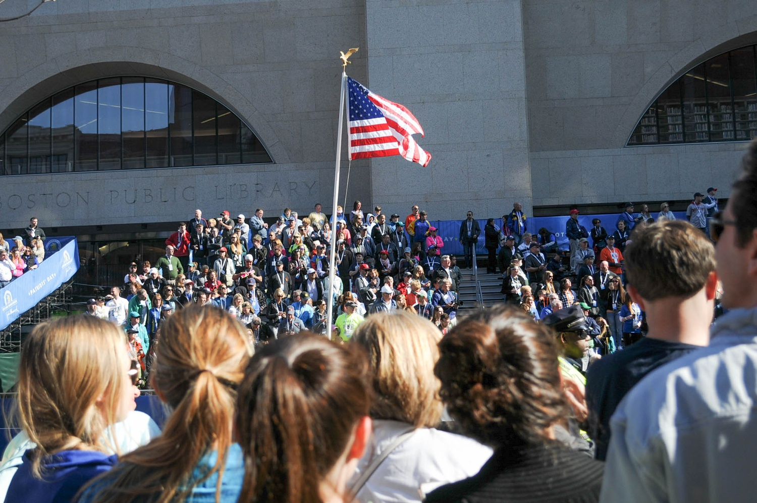 In front of a large stand flanking the finish line at the Boston Public Library, an American flag stands tall in the sun.