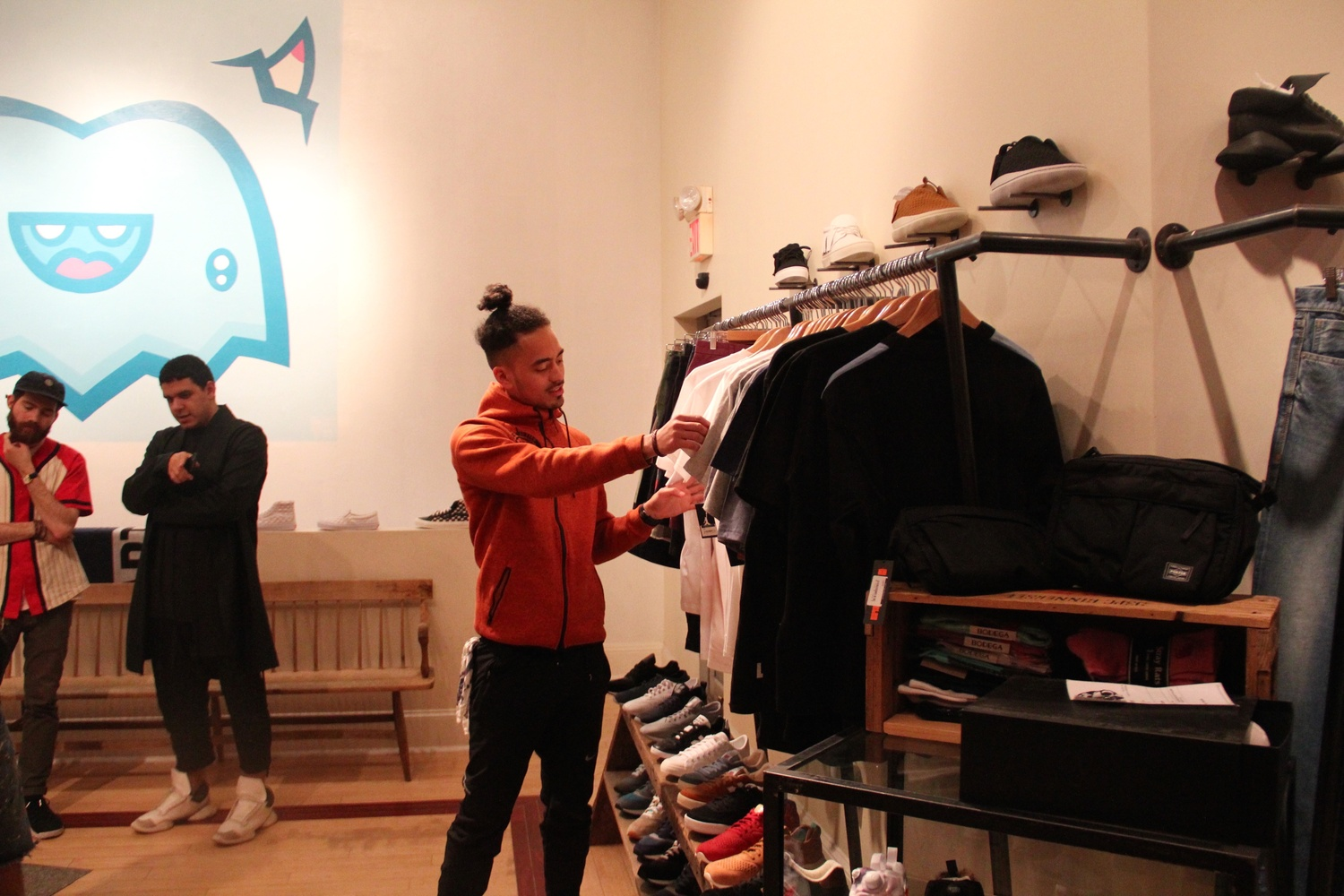 A customer looks through t-shirts. The store sells simple, modern clothes to suit Boston's young, hip demographic. The customers themselves wear the latest styles.