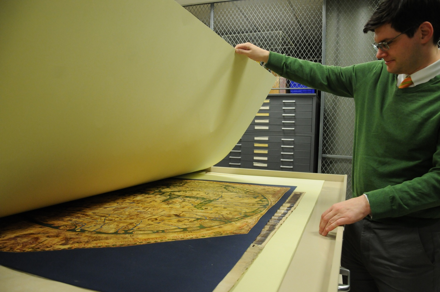 David Weimer, librarian for Cartographic Collections and Learning at the Harvard Map Collection, displays a world map held in Pusey Library.