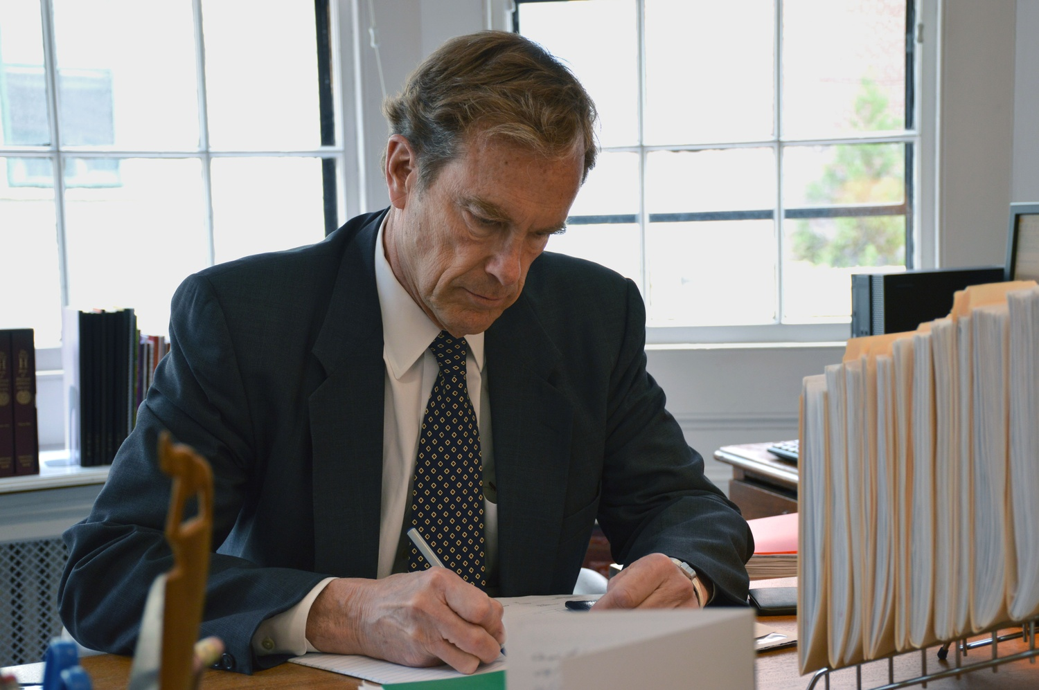 Interim Dean of Student Life Thomas A. Dingman '67 writes at his desk in the Freshman Dean's Office.