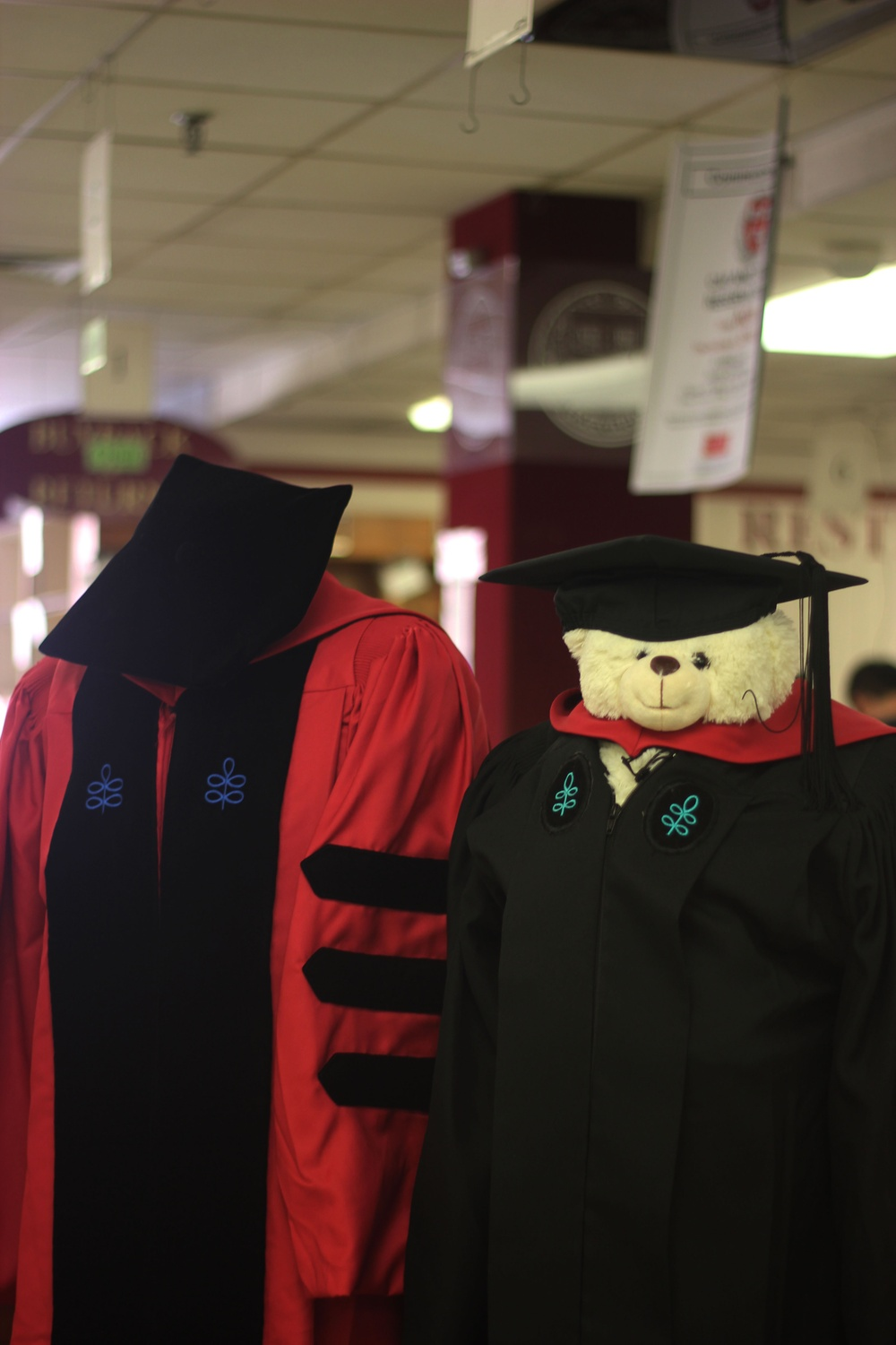A display of caps and gowns is located in front of the Coop's graduation rental station.