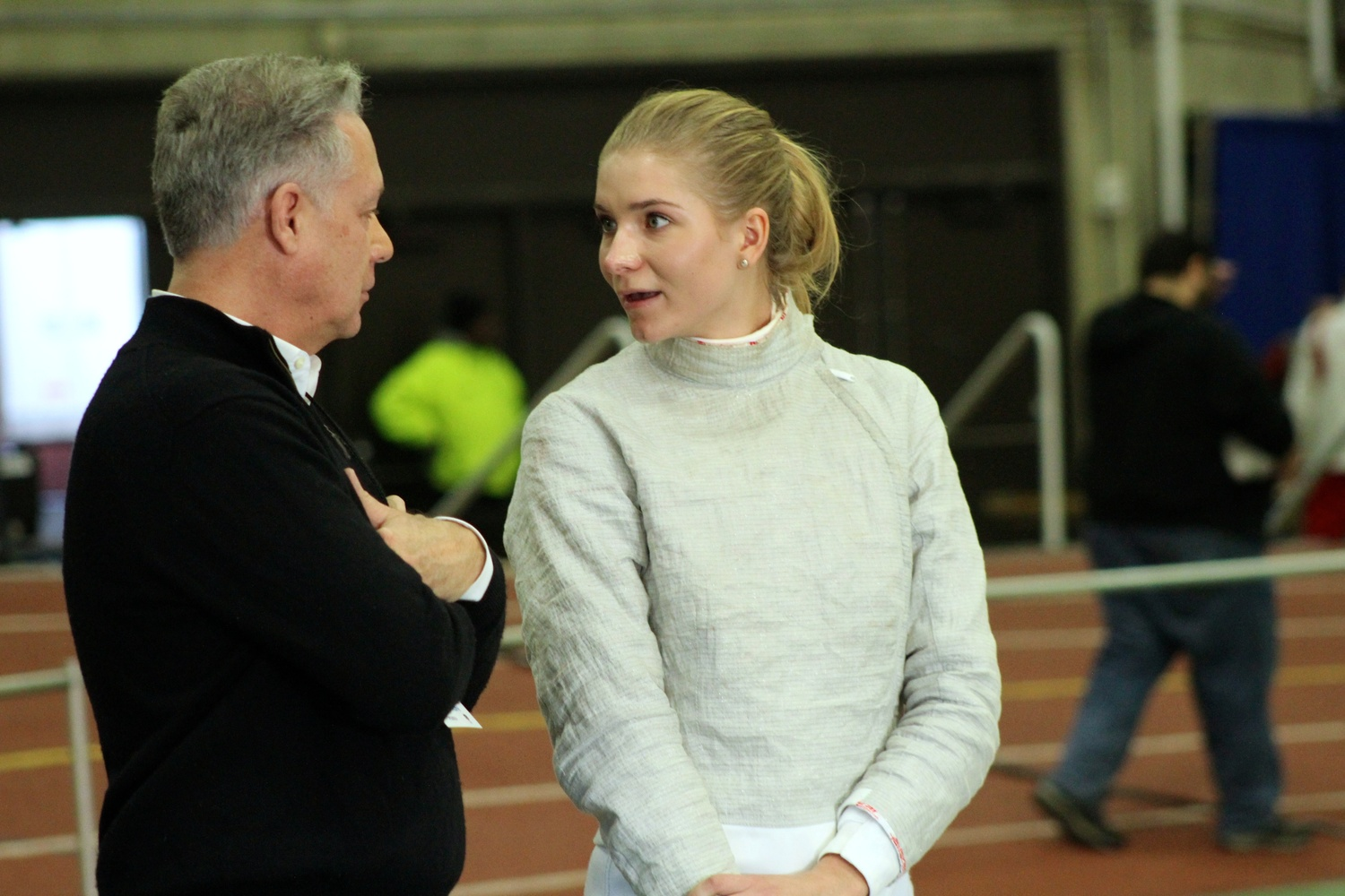 Junior saber fencer Adrienne Jarocki chats with Harvard coach Peter Brand in between bouts at the FIE Sabre Grand Prix. Jarocki claimed her second NCAA title in her collegiate career.
