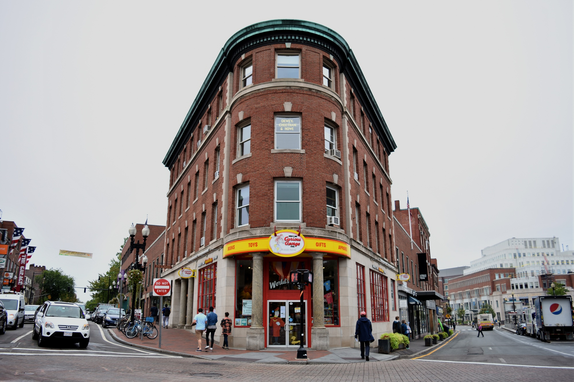 Pedestrians walk by the first Curious George store, a well-known spot in Harvard Square that is now closing down business.