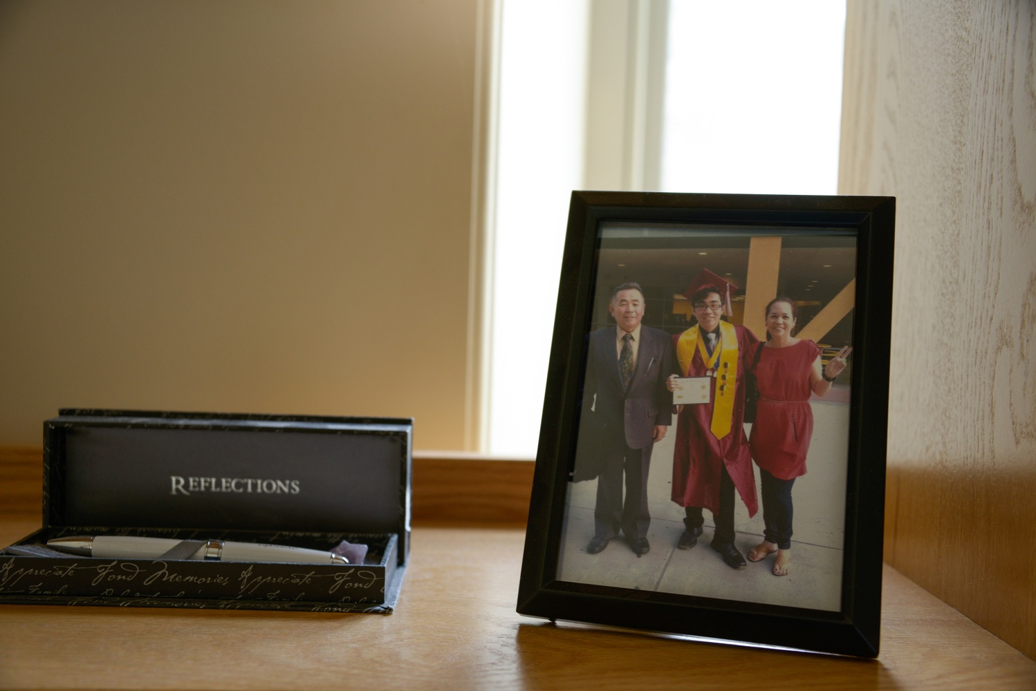 Daishi keeps memories of home, including a graduation photo with his parents and a pen, on his desk.